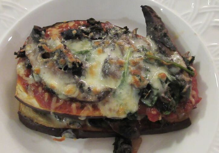 Beautifully browned eggplant strata with melted cheese oozing from layers of eggplant. Served in a whte bowl.